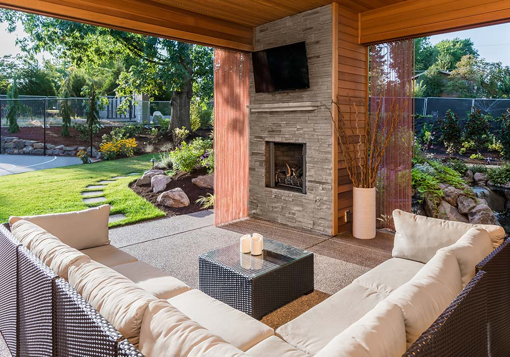 A built-in fireplace with a tv mounted to the wall with a white sectional outside.