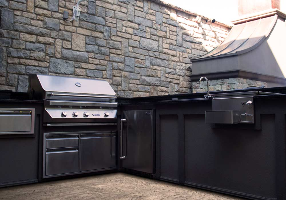 An outdoor kitchen featuring stainless steel appliances.