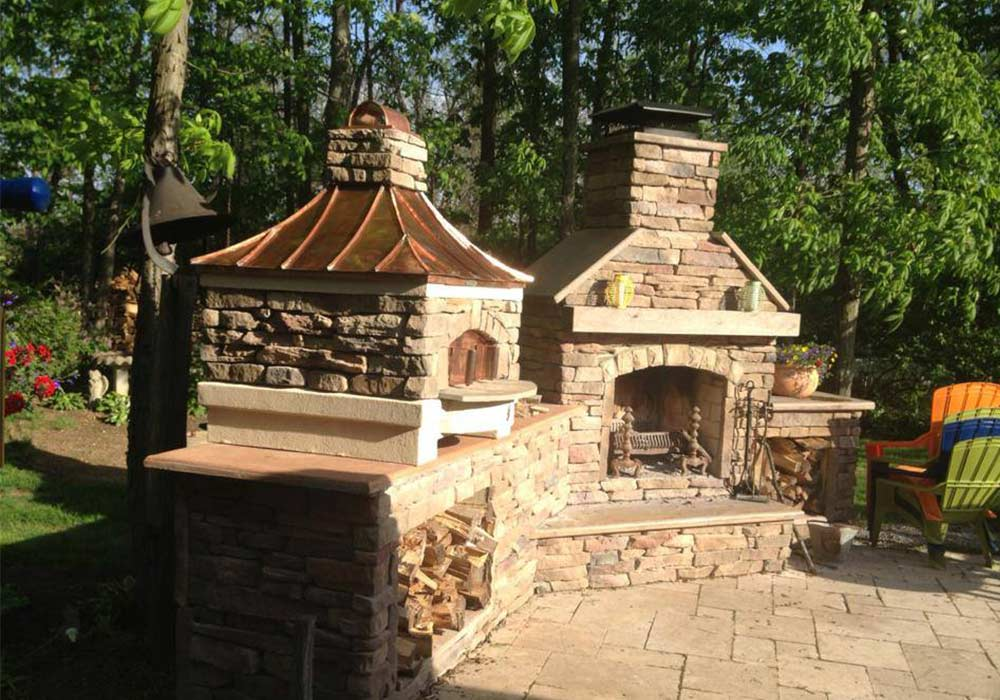 A corner nook outside on the patio featuring an outdoor oven and fireplace.