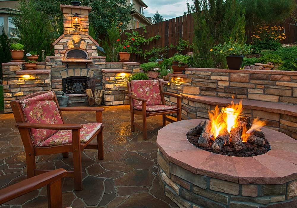 A brick fire pit and matching fireplace for an outdoor patio sitting area.