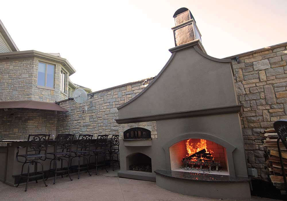 A wood fire oven attached to an outdoor oven to create a 2-in-1 outdoor entertainment area.